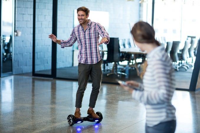 Hoverboard fahren lernen Mann mit Frau als Unterstützung